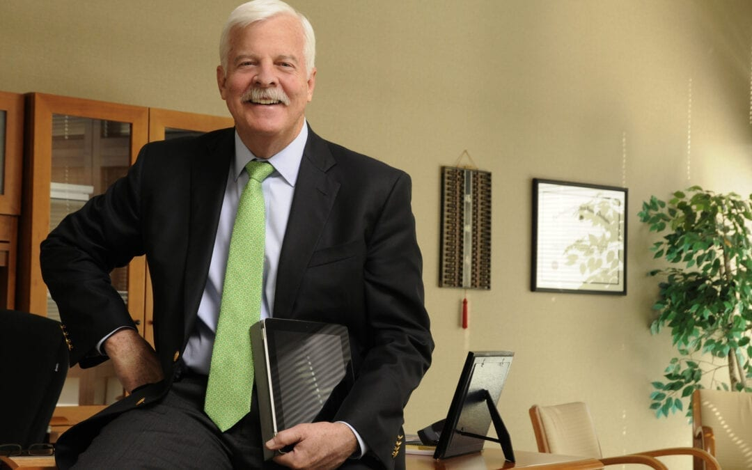 Auditor O'Brien sitting on the edge of his desk and smiling.